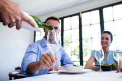 Waiter serving wine to group of friends while having lunch Stock Images