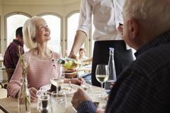 Waiter Serving Wine To Senior Couple In Restaurant Stock Photo