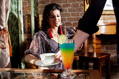 Waiter serving woman with coffee and beverage. In restaurant Royalty Free Stock Photo