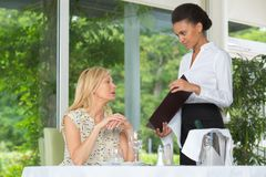 Free Waiter Serving Women In Restaurant Stock Photos - 101670653