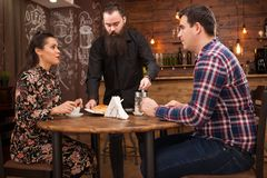 Waiter serving young couple with croissants in vintage coffee shop stock images