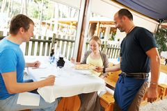 Waiter serving young people in restaurant Royalty Free Stock Photos