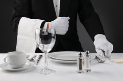 Waiter Setting Formal Dinner Table. Closeup of a waiter in a tuxedo setting a formal dinner table. Shallow depth of field in horizontal format on a light to dark Stock Image