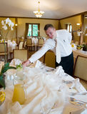 Waiter setting table. Waiter putting jug with water and lemon royalty free stock images