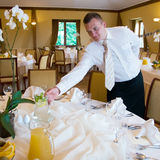 Waiter setting table. Waiter putting jug with water and lemon stock photos