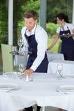 Waiter setting table at restaurant Fotografía de archivo