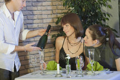 Waiter showing a bottle champagne Stock Image