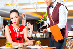 Waiter showing bottle of wine Stock Photo