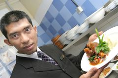 Waiter showing food. Restaurant manager showing food in the kitchen Stock Photos