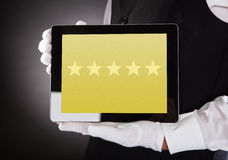 Waiter Showing Rating System On Digital Tablet stock images