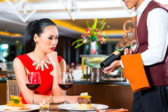 Waiter showing wine in Asian restaurant Royalty Free Stock Images
