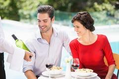 Waiter showing wine bottle to couple Stock Images
