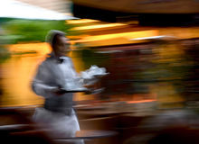 Waiter. In a sidewalk cafe holding tea tray for guests Royalty Free Stock Image