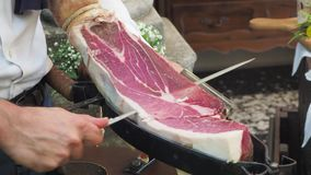 Waiter slices a leg of high quality raw ham. Party time stock video