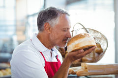Waiter smelling freshly baked bread Royalty Free Stock Photos