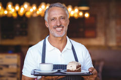 waiter smiling and holding tray Stock Photo