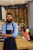 Waiter standing with arms crossed. In the cafe Stock Photos