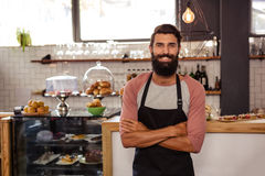 Waiter standing with arms crossed. In the cafe Stock Image