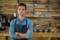 Waiter standing with arms crossed in cafe. Portrait of waiter standing with arms crossed in cafe Royalty Free Stock Photo