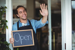 Waiter standing at cafe door holding chalkboard with open sign Stock Photo
