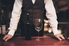 Waiter stands before tray with bottle of wine and empty glass in restaurant. Wine tasting concept. stock photo