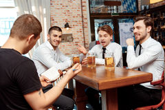 Waiter takes the order. Ready to take orders. Waiter taking orders from young good-looking businessmen sitting by the bar counter Stock Photography