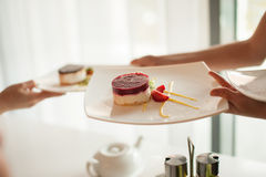 Waiter takes a plate of dessert. Dessert on a white plate, hand a waiter serving plate. Selective Focus Stock Photo