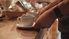 A waiter takes two white cups filled with hot coffee and carries it away. A customer takes two white cups filled with stock footage