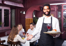 Waiter taking care of adults at cafe table Royalty Free Stock Image