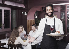 Waiter taking care of adults at cafe table Stock Photos