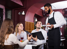 Waiter taking care of adults at cafe table Royalty Free Stock Images