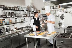 Waiter Taking Customer's Food From Chef. Young waiter taking customer's food from chef in industrial kitchen royalty free stock photos