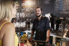 Waiter Taking Female Customer's Order In Coffee Shop stock photo