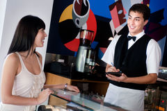 Waiter Taking Order. A young and attractive waiter taking an order from a customer in an indoor restaurant Stock Photo