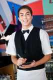 Waiter Taking Order. A young and attractive waiter taking an order in an indoor restaurant Stock Image