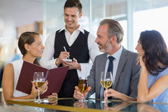 Waiter taking the order from a businessman and his colleagues. In restaurant Royalty Free Stock Photos