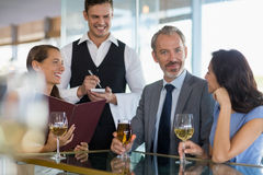 Waiter taking the order from a businessman and his colleagues Royalty Free Stock Photos