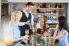Waiter taking the order from a businessman and his colleagues Stock Photos