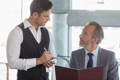 Waiter taking the order from a businessman. In restaurant Royalty Free Stock Photography