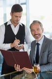 Waiter taking the order from a businessman. In restaurant Stock Photography
