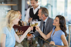 Waiter taking the order while colleagues toasting glasses of wine. In restaurant Royalty Free Stock Photos