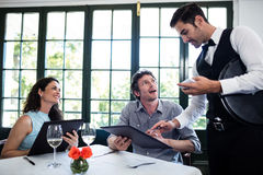 Waiter taking an order for a couple. In a restaurant Royalty Free Stock Images