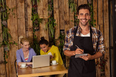 A waiter is taking the order in front of the two friends. In a coffee shop Stock Images