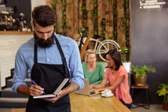 Waiter taking order in his book Stock Photo