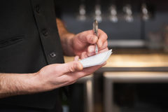 Waiter taking order in his notepad. In a bar Royalty Free Stock Photo