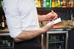 Waiter taking order in his notepad. In a bar Stock Photos