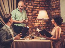 Waiter taking order from stylish wealthy couple Royalty Free Stock Photos