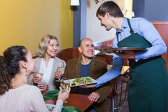 Waiter taking order at table of people. Having dinner together Stock Image