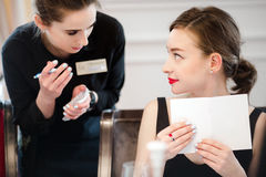 Waiter taking order. Young server taking order while talking with elegant woman Royalty Free Stock Image