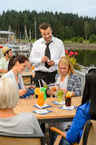 Waiter taking orders sidewalk bar from women Stock Image